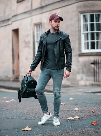 Come indossare e abbinare: giacca da moto in pelle nera, t-shirt manica lunga grigio scuro, jeans aderenti grigi, sneakers basse in pelle bianche