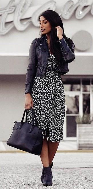 Come indossare e abbinare: giacca da moto in pelle nera, vestito a tubino stampato nero e bianco, stivaletti in pelle neri, borsa shopping in pelle nera