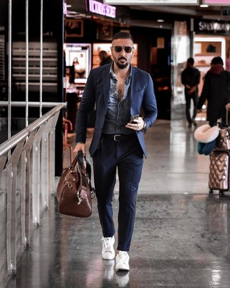 Come indossare e abbinare un borsone in pelle marrone: Per un outfit della massima comodità, combina una giacca di jeans blu con un borsone in pelle marrone. Rifinisci il completo con un paio di sneakers basse in pelle bianche.