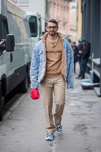 Come indossare e abbinare: giacca di jeans azzurra, maglione girocollo stampato marrone chiaro, pantaloni eleganti marrone chiaro, scarpe sportive multicolori