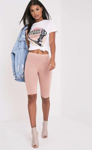 Come indossare: giacca di jeans strappata azzurra, t-shirt girocollo stampata bianca e rosa, pantaloncini ciclisti rosa, stivaletti in pelle tagliati beige