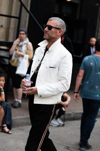 Come indossare: giacca di jeans bianca, t-shirt girocollo nera, pantaloni sportivi a righe verticali neri, occhiali da sole neri
