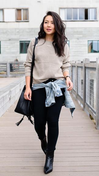 Come indossare: giacca di jeans azzurra, maglione girocollo beige, jeans aderenti neri, stivaletti in pelle neri