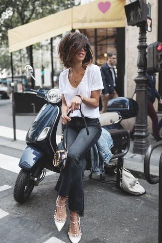Come indossare: giacca di jeans azzurra, t-shirt con scollo a v bianca, jeans a campana neri, décolleté in pelle con borchie bianchi