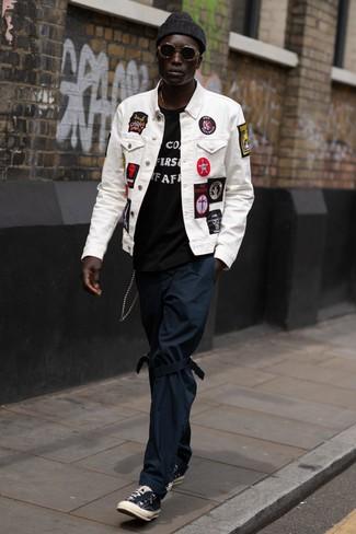 Come indossare: giacca di jeans ricamata bianca, t-shirt girocollo stampata nera e bianca, chino blu scuro, sneakers basse di tela nere