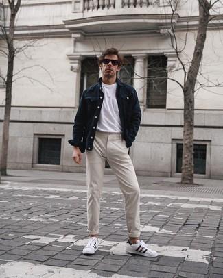 Come indossare e abbinare chino beige: Opta per una giacca di jeans blu scuro e chino beige per un fantastico look da sfoggiare nel weekend. Per un look più rilassato, scegli un paio di sneakers basse in pelle bianche e nere come calzature.