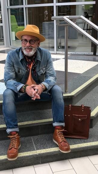 Come indossare e abbinare: giacca di jeans blu, t-shirt girocollo arancione, jeans aderenti blu, stivali da lavoro in pelle marroni