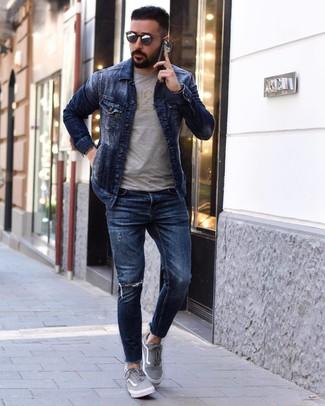 Come indossare e abbinare: giacca di jeans blu scuro, t-shirt girocollo stampata grigia, jeans aderenti strappati blu scuro, sneakers basse di tela grigie