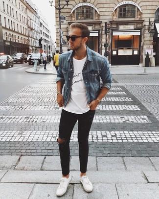 Come indossare e abbinare: giacca di jeans blu, t-shirt girocollo stampata bianca e nera, jeans aderenti strappati neri, sneakers basse in pelle bianche