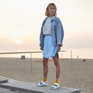 Trend da donna 2020 in modo rilassato: Prova a combinare una giacca di jeans azzurra con una minigonna azzurra per un look comfy-casual. Mettiti un paio di sandali piatti in pelle bianchi per un tocco più rilassato.