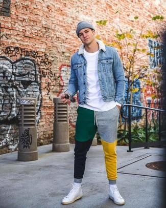 Come indossare e abbinare: giacca di jeans blu, t-shirt manica lunga bianca, pantaloni sportivi multicolori, sneakers alte in pelle bianche