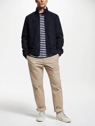Come indossare e abbinare: giacca harrington blu scuro, t-shirt girocollo a righe orizzontali bianca e blu scuro, chino beige, sneakers basse in pelle bianche