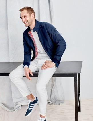 Come indossare e abbinare: giacca harrington blu scuro, t-shirt manica lunga grigia, chino bianchi, sneakers basse in pelle scamosciata blu scuro