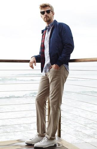 Come indossare e abbinare: giacca harrington blu scuro, camicia a maniche lunghe scozzese bianca e blu scuro, chino beige, sneakers basse in pelle bianche