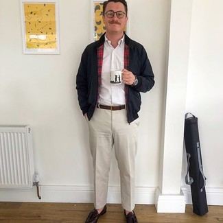 Come indossare e abbinare: giacca harrington nera, camicia a maniche lunghe bianca, pantaloni eleganti beige, mocassini con nappine in pelle marrone scuro