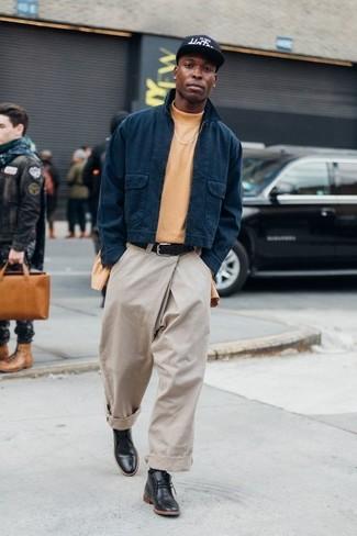 Come indossare e abbinare chino beige: Per creare un adatto a un pranzo con gli amici nel weekend scegli un outfit composto da una giacca harrington blu scuro e chino beige. Completa questo look con un paio di chukka in pelle nere.