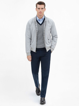 Come indossare e abbinare: giacca harrington grigia, maglione con scollo a v grigio, camicia a maniche lunghe a quadretti azzurra, pantaloni eleganti blu scuro