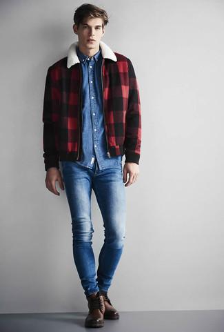 Come indossare e abbinare: giacca harrington a quadri rossa e nera, camicia di jeans blu, jeans aderenti blu, stivali casual in pelle marroni