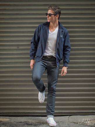 Come indossare e abbinare: giacca harrington blu scuro, t-shirt con scollo a v bianca, jeans grigio scuro, sneakers basse di tela bianche