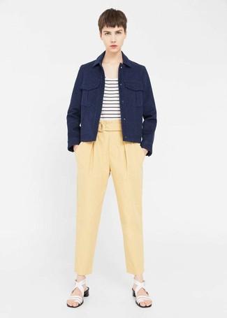 Come indossare: giacca militare blu scuro, t-shirt girocollo a righe orizzontali bianca e nera, pantaloni stretti in fondo gialli, sandali con tacco in pelle bianchi