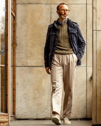 Come indossare e abbinare: giacca militare blu scuro, maglione a trecce verde oliva, pantaloni eleganti beige, sneakers basse in pelle scamosciata beige