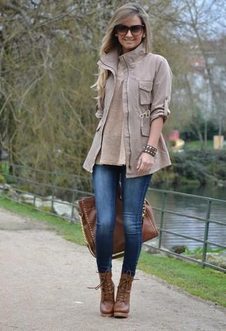Come indossare: giacca militare grigia, maglione girocollo beige, leggings di jeans blu, stivaletti con lacci in pelle marroni