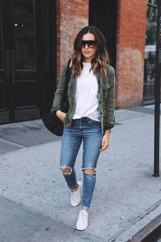 Come indossare: giacca militare verde scuro, t-shirt girocollo bianca, jeans aderenti strappati blu, sneakers basse di tela bianche