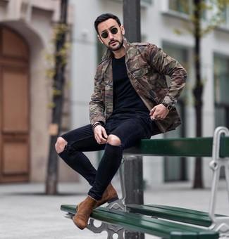 Come indossare e abbinare: giacca militare mimetica verde oliva, t-shirt girocollo nera, jeans aderenti strappati neri, stivali chelsea in pelle scamosciata marroni
