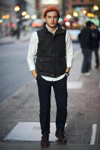Come indossare e abbinare: gilet nero, camicia a maniche lunghe beige, chino blu scuro, stivali da lavoro in pelle marrone scuro