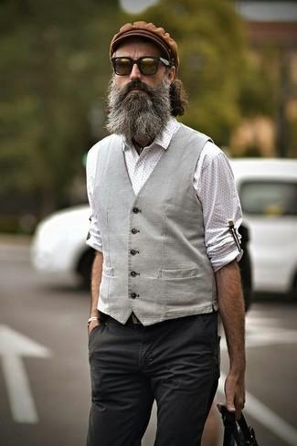 Come indossare: gilet grigio, camicia a maniche lunghe a pois bianca, chino grigio scuro, coppola marrone
