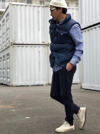 Come indossare e abbinare: gilet trapuntato blu scuro, camicia a maniche lunghe a quadretti blu scuro e bianca, jeans di velluto a coste neri, sneakers basse di tela bianche