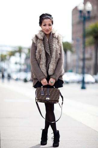 Come indossare e abbinare: gilet di pelliccia grigio, cardigan aperto lavorato a maglia grigio, gonna a pieghe nera, stivaletti in pelle scamosciata neri