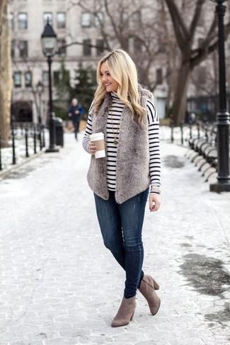 Come indossare: gilet di pelliccia grigio, dolcevita a righe orizzontali bianco e nero, jeans aderenti blu scuro, stivaletti in pelle scamosciata grigi