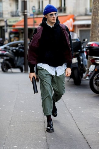 Come indossare: gilet viola melanzana, felpa con cappuccio nera, camicia a maniche lunghe a righe verticali azzurra, chino verde scuro