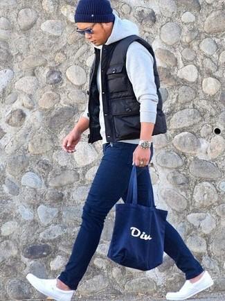 Come indossare e abbinare sneakers senza lacci di tela bianche: Punta su un gilet trapuntato nero e jeans aderenti blu scuro per una sensazione di semplicità e spensieratezza. Sneakers senza lacci di tela bianche doneranno eleganza a un look altrimenti semplice.