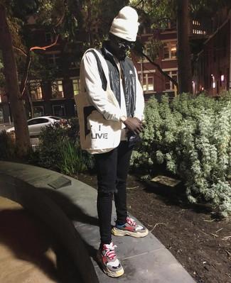 Come indossare e abbinare: gilet nero, felpa bianca, jeans aderenti strappati neri, scarpe sportive multicolori