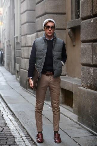 Come indossare e abbinare: gilet trapuntato grigio, maglione girocollo nero, camicia a maniche lunghe bianca, chino marroni