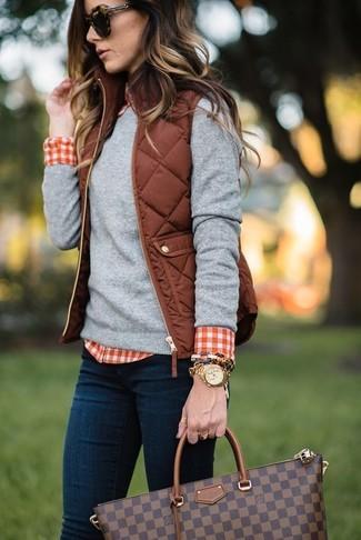 Come indossare: gilet trapuntato marrone, maglione girocollo grigio, camicia elegante a quadretti rossa e bianca, jeans aderenti blu scuro