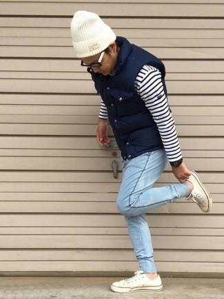 Come indossare e abbinare: gilet trapuntato blu scuro, maglione girocollo a righe orizzontali bianco e blu scuro, jeans azzurri, sneakers basse bianche