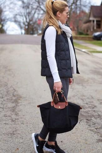 Come indossare: gilet trapuntato nero, maglione girocollo bianco, leggings grigio scuro, scarpe sportive nere