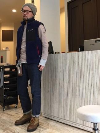 Come indossare e abbinare: gilet di pile blu scuro, maglione girocollo beige, t-shirt manica lunga grigia, jeans blu scuro