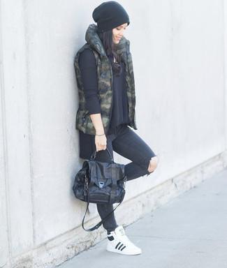 Come indossare: gilet mimetico verde scuro, maglione oversize nero, jeans aderenti strappati grigio scuro, sneakers alte in pelle bianche