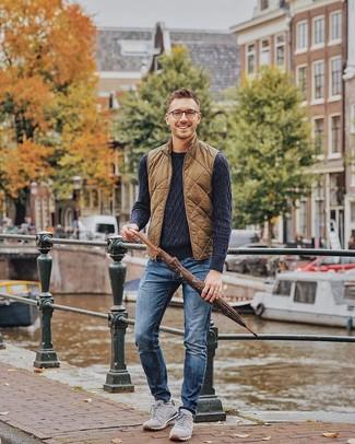 Come indossare e abbinare: gilet trapuntato marrone, maglione a trecce blu scuro, jeans blu, scarpe sportive in pelle scamosciata grigie