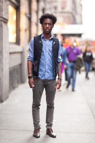 Come indossare e abbinare: gilet nero, camicia a maniche lunghe azzurra, jeans grigi, scarpe oxford in pelle marroni