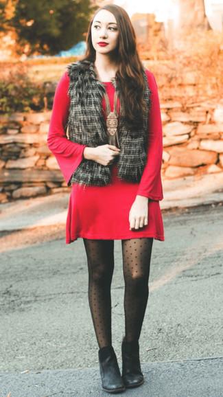 Come indossare: gilet di pelliccia nero, vestito di maglia rosso, stivaletti in pelle neri, collant a pois nero