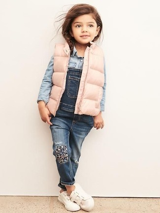 Come indossare e abbinare: gilet rosa, camicia a maniche lunghe di jeans azzurra, salopette di jeans blu, sneakers bianche