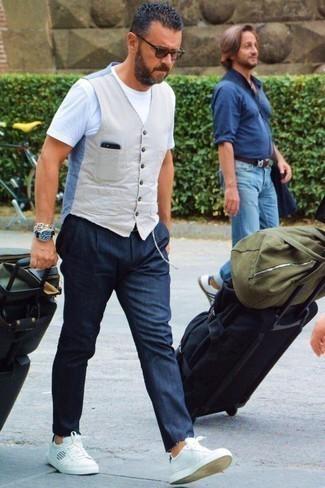 Come indossare e abbinare jeans blu scuro: Potresti abbinare un gilet beige con jeans blu scuro per essere sofisticato e di classe. Per un look più rilassato, scegli un paio di sneakers basse in pelle bianche.