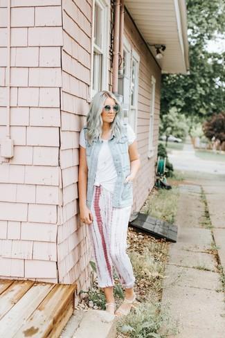 Come indossare: gilet di jeans azzurro, t-shirt girocollo bianca, pantaloni sportivi effetto tie-dye bianchi, sandali piatti di gomma trasparenti