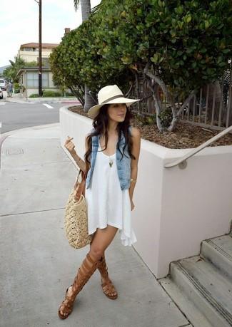 Come indossare: gilet di jeans azzurro, vestito scampanato bianco, sandali gladiatore alti in pelle marroni, borsa shopping all'uncinetto beige