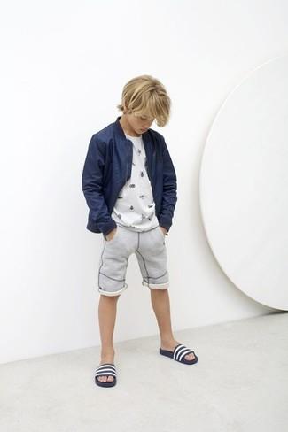 Come indossare e abbinare: giubbotto bomber blu scuro, t-shirt bianca, pantaloncini grigi, sandali blu scuro e bianchi
